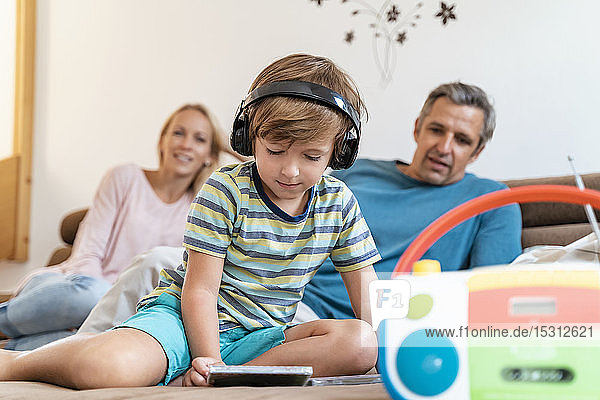 Family on couch at home with boy listening to music with headphones