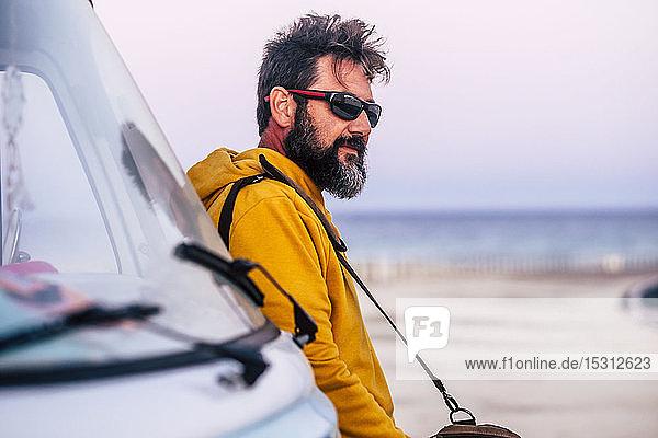 Mann mit gelbem Kapuzenpullover und braunem Korb  der sich an einen Lieferwagen lehnt