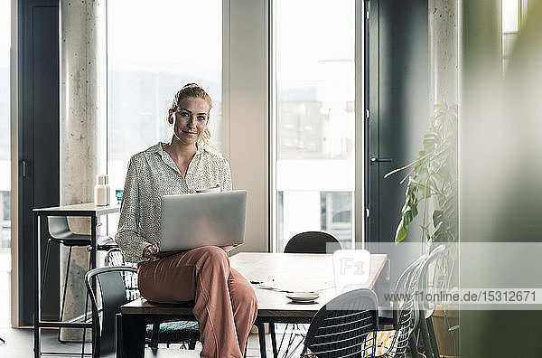Portrait of businesswoman sitting on table in office with laptop