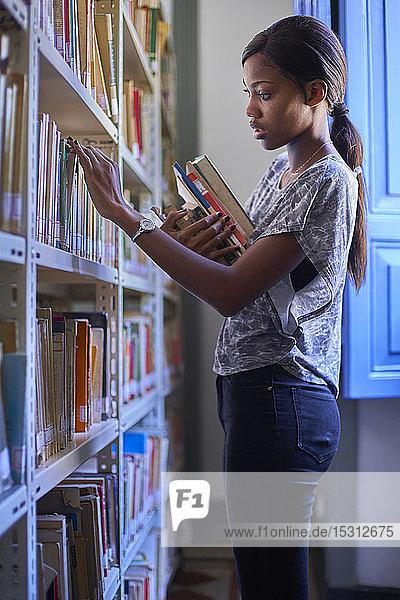 Junge Frau prüft die Bücher in den Regalen der Nationalbibliothek  Maputo  Mosambik