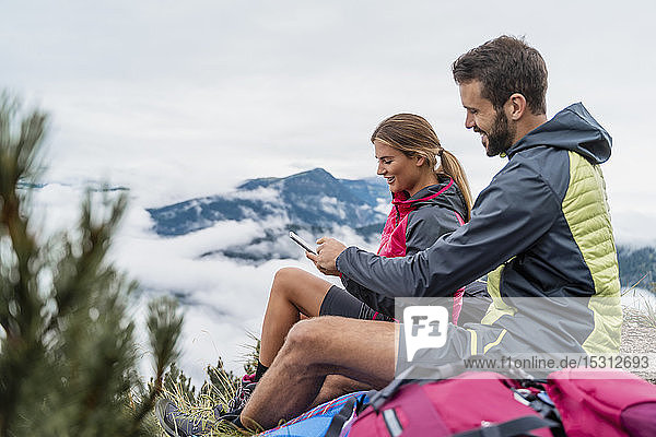 Young couple on a hiking trip in the mountains having a break using cell phone  Herzogstand  Bavaria  Germany