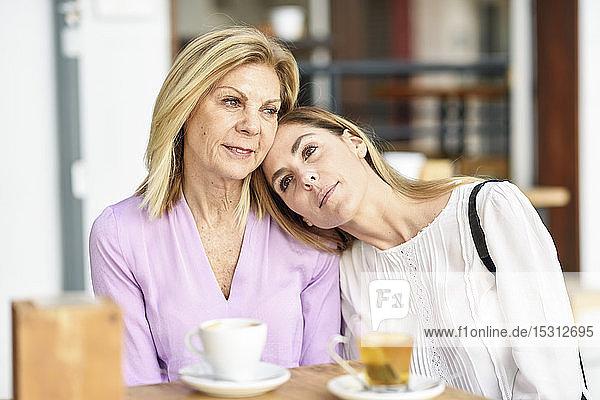 Eine reife Frau mit ihrer Tochter sitzt an einem Tisch im Freien in einem Café