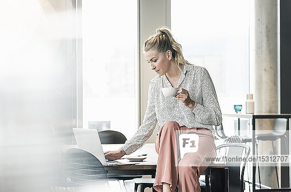 Businesswoman with cup of coffee sitting on table in office using laptop