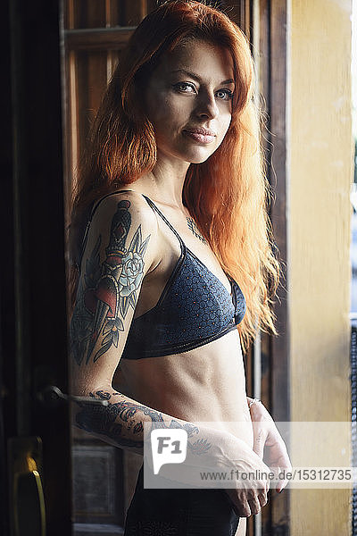 Red-haired tattooed woman in lingerie at home near the window