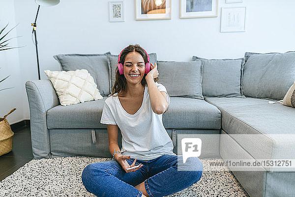 Glückliche junge Frau sitzt auf dem Boden im Wohnzimmer und hört Musik mit ihrem Handy
