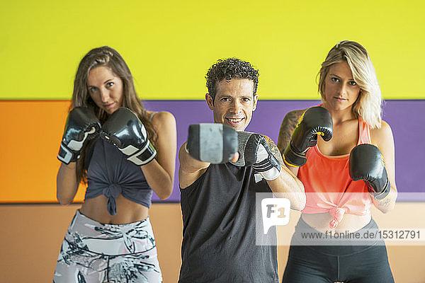 Porträt von drei Athleten mit Boxhandschuhen  die in einer Turnhalle posieren
