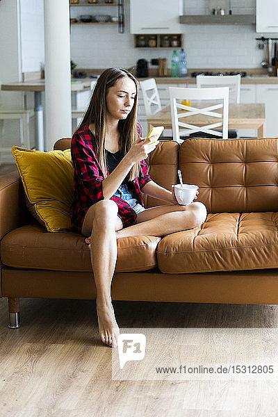 Junge Frau  die zu Hause auf einer Couch telefoniert