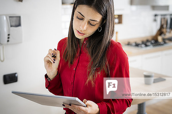 Young businesswoman using graphics tablet at home