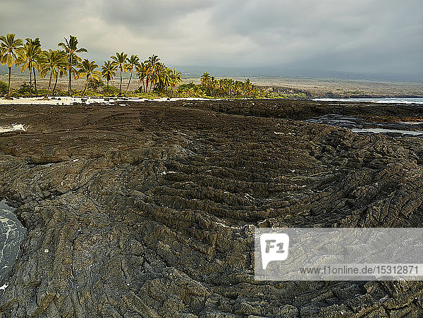 Volcanic rocks and trees at Puuhonua O Honaunau National Historical Park against cloudy sky