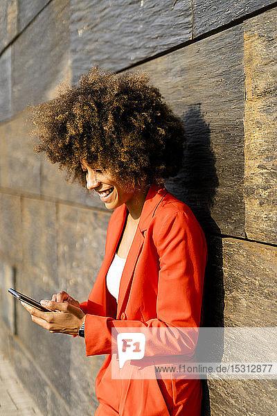 Glückliche junge Frau in modischem roten Hosenanzug lehnt an der Wand und schaut auf Handy
