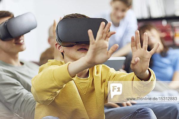 Kleiner Junge spielt mit VR-Brille  sitzt mit seiner Familie auf dem Sofa