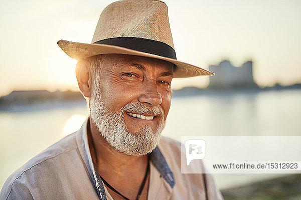 Porträt eines lächelnden älteren Mannes mit Sommerhut am Flussufer bei Sonnenuntergang