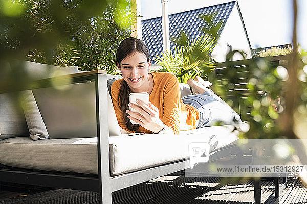 Junge Frau liegt auf einer Couch auf der Terrasse und benutzt Handy und Laptop