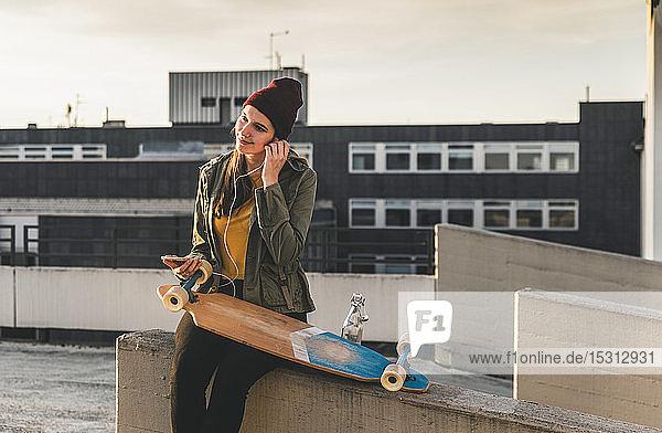 Stilvolle junge Frau mit Skateboard  Kopfhörern und Mobiltelefon auf dem Parkdeck