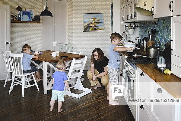 Mutter mit ihren drei Söhnen in der Küche