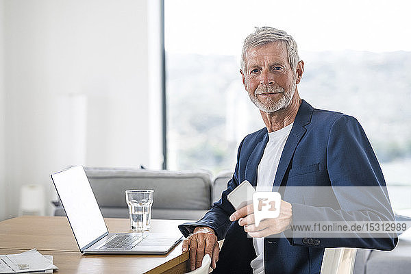 Portrait of senior businessman with laptop and cell phone sitting at desk at home