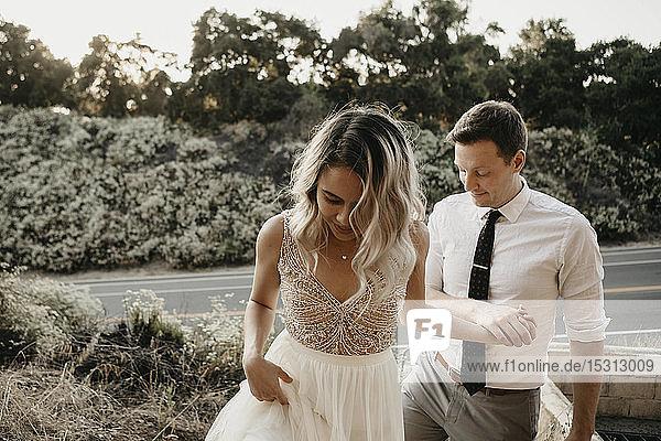 Zärtliches Händchenhalten von Braut und Bräutigam im Freien
