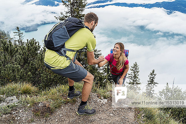 Young man helping girlfriend on a hiking trip in the mountains  Herzogstand  Bavaria  Germany
