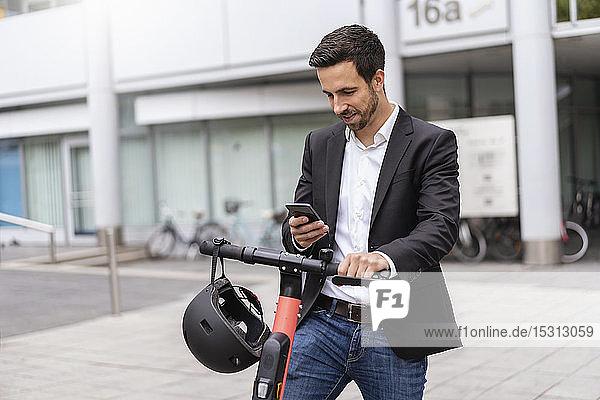 Geschäftsmann mit E-Scooter mit Mobiltelefon in der Stadt