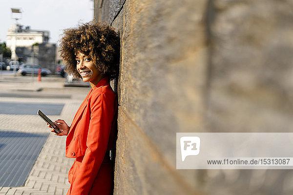 Porträt einer lächelnden jungen Frau mit Handy in modischem roten Hosenanzug an der Wand lehnend