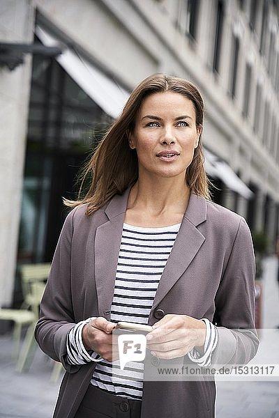 Porträt einer Geschäftsfrau mit Smartphone in der Stadt
