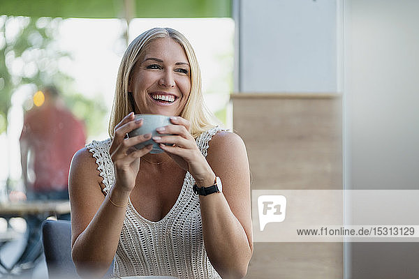Portrait of happy blond woman drinking coffee in a cafe