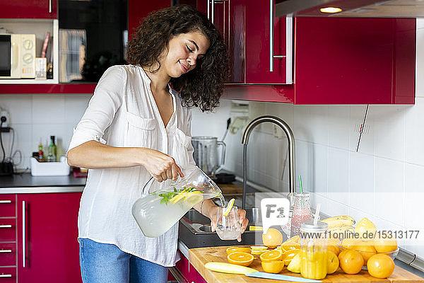 Junge Frau gießt zu Hause in der Küche Limonade in ein Glas