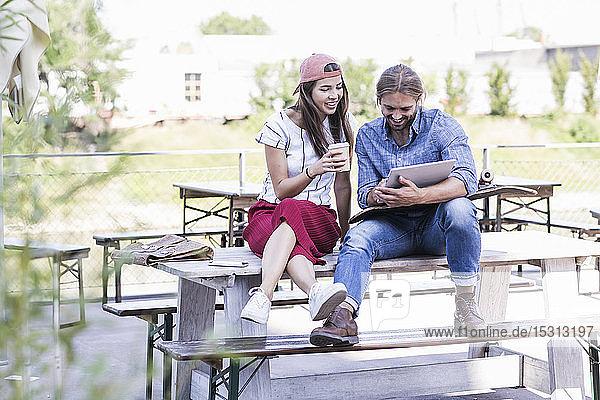 Junges Paar sitzt mit Tablette am Tisch in einem Biergarten