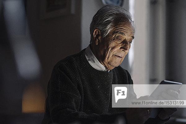 Älterer Mann benutzt Tablette zu Hause