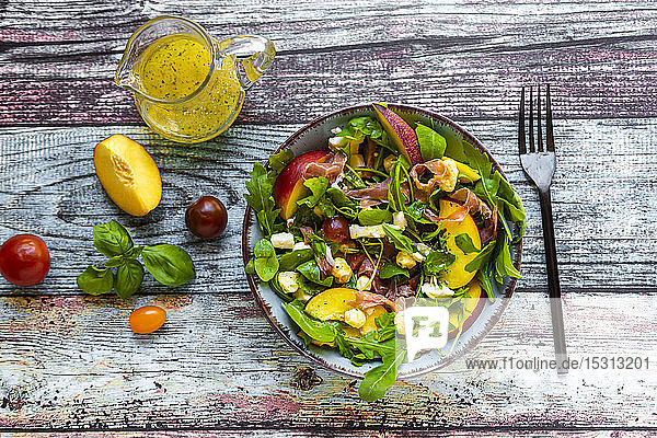 Directly above view of fresh salad bowl with fork and pitcher on table
