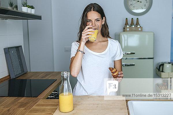Junge Frau beim Frühstück mit Saft und Croissant in der Küche