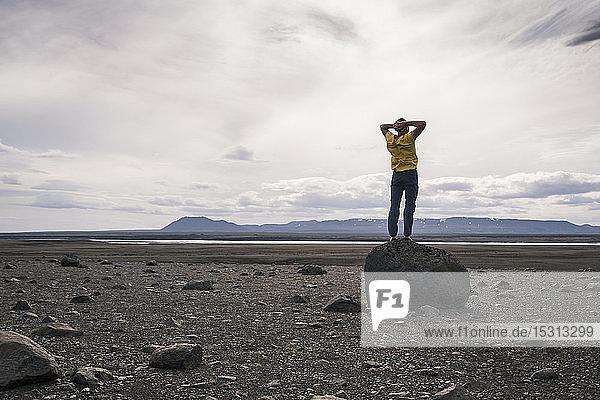 Erwachsener Mann steht auf einem Felsen im vulkanischen Hochland von Island