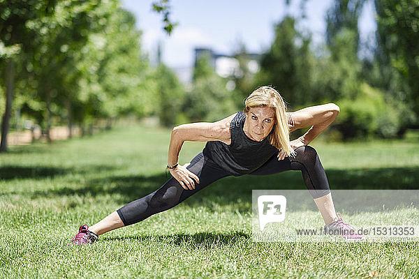 Eine reife Frau übt auf einer Wiese in einem Park