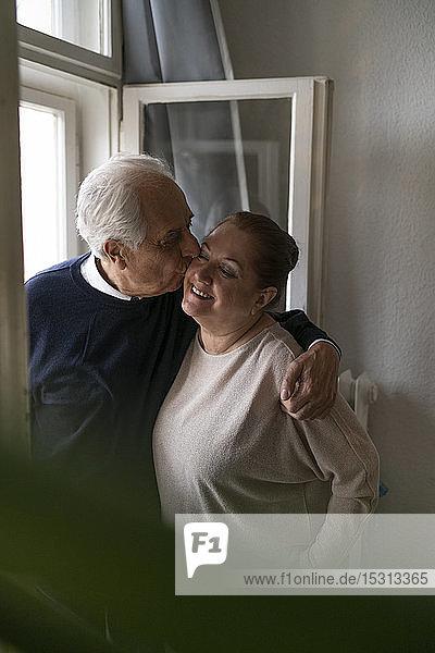 Glückliches älteres Paar küsst sich zu Hause am Fenster