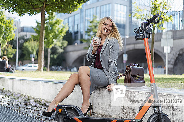 Portrait of blond businesswoman with electric scooter sitting on a wall drinking coffee to go