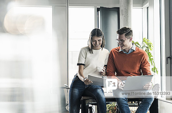 Casual businessman and woman with laptop and documents meeting in office
