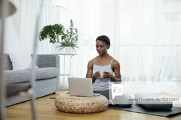 Woman sitting on gym mat at home using laptop