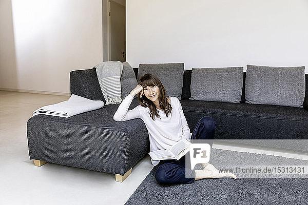 Porträt einer entspannten Frau mit Buch im Wohnzimmer