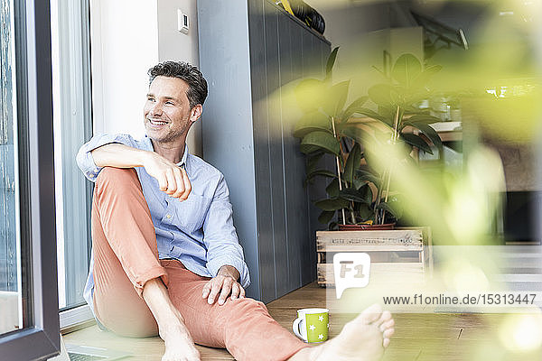 Mature man relaxing at home with a cup of coffee