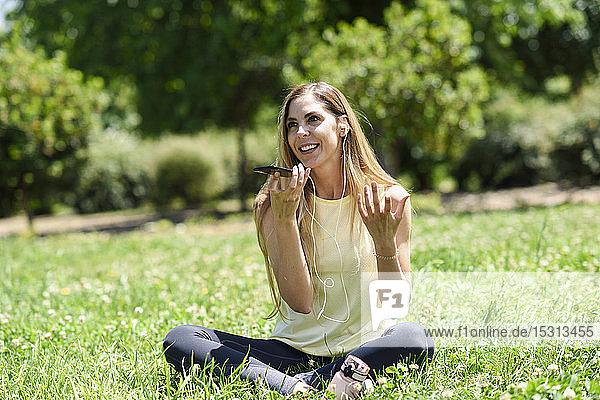 Frau  die ihr Smartphone benutzt und sich nach dem Sport im Gras eines Parks ausruht