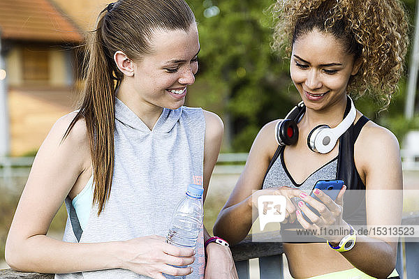 Two smiling sporty young women checking cell phone