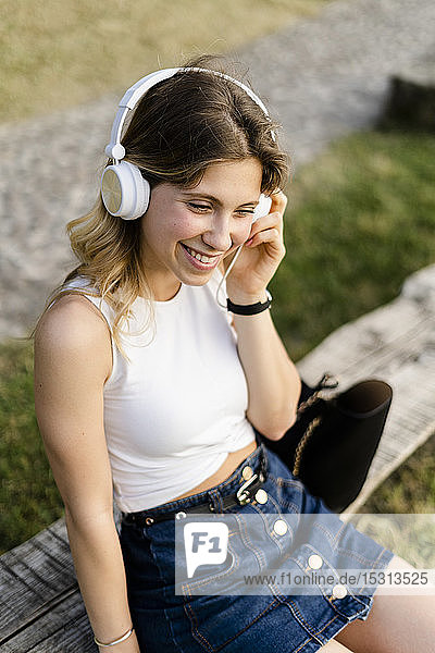 Porträt einer glücklichen jungen Frau  die mit Kopfhörern Musik hört