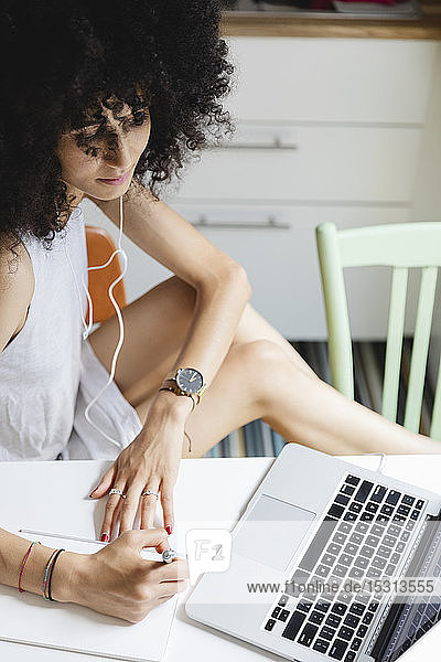 Junge Frau lernt mit ihrem Laptop