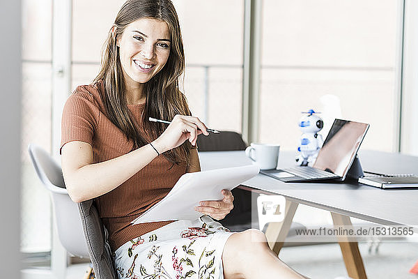 Portrait of smiling young businesswoman sitting at desk in office taking notes