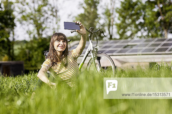 Relaxed woman sitting on a meadow with bicycle taking a selfie