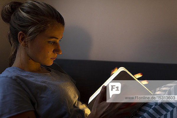 Young woman reading illuminated book on couch at home