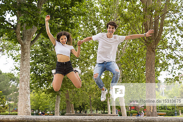Young couple jumping from a wall at the park