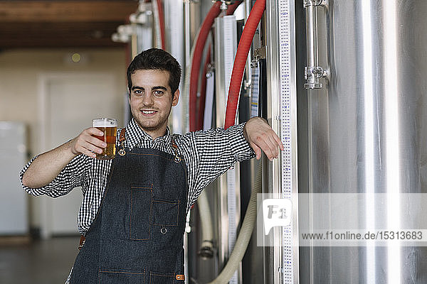Portrait of confident young man holding beer glass at a brewery