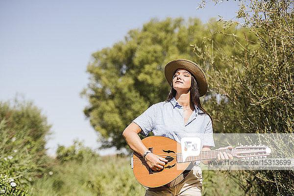 Junge Frau spielt Gitarre  geht auf einem Holzsteg