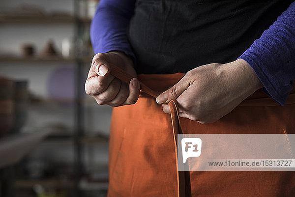 Frauenhände binden Schürze